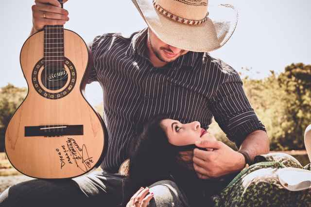 woman in green top with man in black long sleeved shirt holding autographed brown guitar